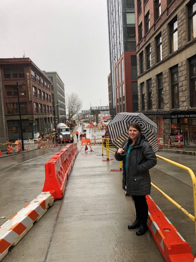 Liz stands on Columbia Street facing east with construction crews and activity in the background.